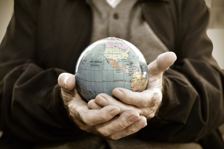 asylum: closeup of an old caucasian man with a world globe in his hands, with a dramatic effect Stock Photo