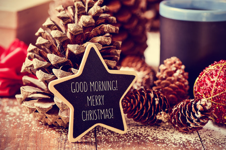 christmas morning: the text good morning merry christmas written in a star-shaped blackboard on a rustic wooden surface with some pinecones, a red christmas bauble and a mug with tea or coffee Stock Photo