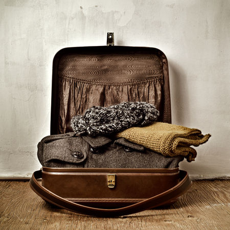 knit cap: an old brown suitcase with some warm clothing, such as an overcoat, a scarf and a knit cap