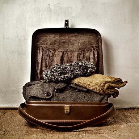 maleta: una vieja maleta marrón con un poco de ropa caliente, tal como un abrigo, una bufanda y un gorro de lana Foto de archivo