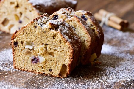 fruitcake: closeup of some pieces of fruitcake for christmas time sprinkled with icing sugar, on a rustic wooden table Stock Photo
