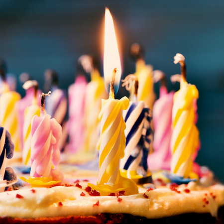 closeup of some unlit candles and just a lit candle after blowing out the cake, filtered Foto de archivo