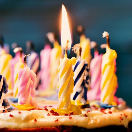torta candeline: primo piano di alcune candele spente e solo una candela accesa dopo aver soffiato la torta, filtrato Archivio Fotografico