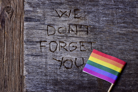 sexual orientation: the text we do not forget you carved in an old wooden surface and a gay pride flag Stock Photo
