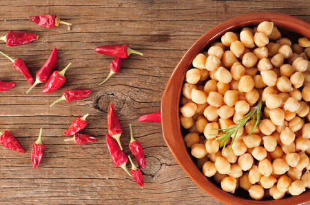 red cooked: high-angle shot of an earthenware bowl with cooked chickpeas and some red chili peppers on a rustic wooden table
