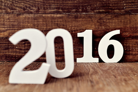 0 1 year: three-dimensional white numbers forming the number 2016, as the new year, on a rustic wooden surface