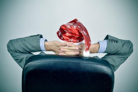 un jeune homme d'affaires caucasien vu par derrière avec un chapeau de Santa de détente dans son fauteuil de bureau après un bureau fête de noël