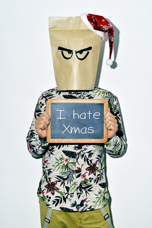 a young man dressing casual wear with a paper bag in his head and a santa hat in the top shows a chalkboard with the text I hate Xmas written in it