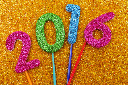 0 1 year: glittering numbers of different colors forming the number 2016, as the new year, on a shiny golden background
