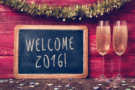 happy new year: a chalkboard with the text welcome 2016 written in it, some confetti and a pair of glasses with champagne on a red rustic wooden background ornamented with tinsel Stock Photo
