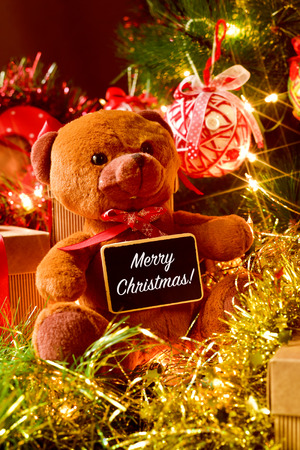 christmas present: closeup of a brown teddy bear with a chalkboard with the text merry christmas, and some gifts under a christmas tree ornamented with lights, balls and tinsel Stock Photo