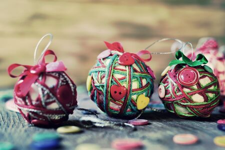 notions: closeup of some different handmade christmas balls, made with string, ribbon and buttons, on a rustic wooden surface, with a filter effect Stock Photo