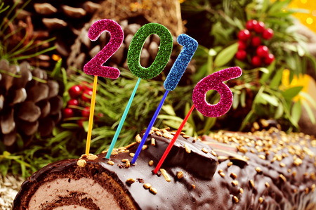yule log: a yule log cake, traditional of christmas time, topped with glittering numbers of different colors forming the number 2016, as the new year Stock Photo