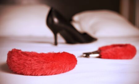 sex traffic: closeup of a pair of red sexy fluffy handcuffs and a black high heeled shoe on a bed, with a filter effect