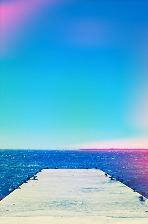 mooring bollards: picture of a concrete dock with some mooring bollards in the Mediterranean sea, with a light leak effect