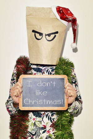 dont: a young man dressing casual wear with a paper bag in his head and a santa hat in the top and some tinsel in his shoulders shows a chalkboard with the text I dont like christmas