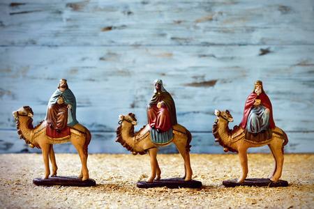 les trois rois dans leurs chameaux portant leurs cadeaux pour l'enfant Jésus sur une scène de nativité rustique