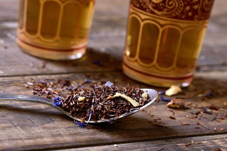 thirstiness: closeup of a spoon with rooibos tea mixed with flowers, dry fruits and herbs, on a rustic wooden table with some ornamented glasses in the background Stock Photo