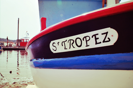 closeup of the hull of a boat  moored in Saint-Tropez, France, with the text St. Tropez written in it, with a retro effect