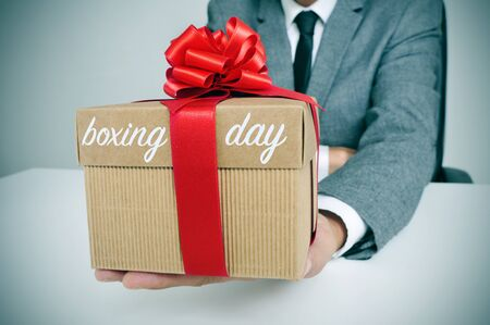 boxing day: a young caucasian man in suit sitting at his office holding a gift tied with a red ribbon and the text boxing day