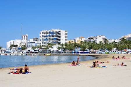 vacationers: San Antonio, Spain - June 19, 2015:  Sunbathers at Arenal Beach in San Antonio, Ibiza Island, Spain. Ibiza is a well-known summer tourist destination in Europe
