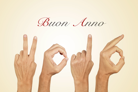 anno: man hands forming the number 2016, as the new year, and the text buon anno, happy new year in italian, on a beige background