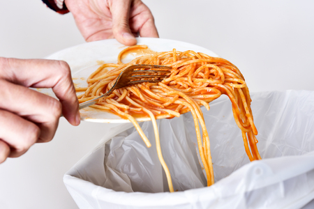 food waste: closeup of a young man throwing the leftover of a plate of spaghetti to the trash bin
