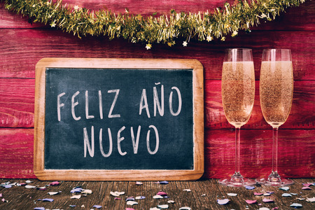 ano: a chalkboard with the text feliz ano nuevo, happy new year written in spanish, some confetti and a pair of glasses with champagne on a red rustic wooden background ornamented with tinsel