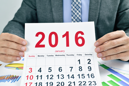 headman: a young caucasian businessman at his office desk full of charts shows a 2016 calendar Stock Photo