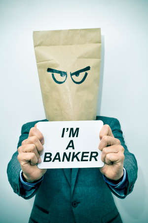 loaning: a young caucasian businessman with a paper bag in his head shows a signboard with the text I am a banker, with a dramatic effect