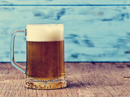 of yesteryear: refreshing beer served in a glass mug on a rustic wooden surface, against a blue rustic wooden background