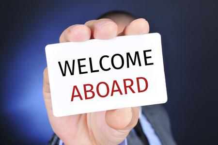 bienvenida: un joven hombre de negocios caucásico muestra un letrero con el texto de bienvenida a bordo Foto de archivo