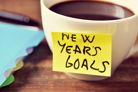 cerca de una taza de café con una nota amarilla pegajosa con el texto de año nuevo los objetivos por escrito en ella y un cuaderno y un lápiz sobre una mesa de madera rústica