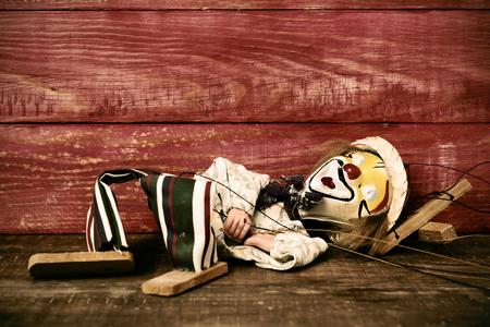 marioneta de madera: una vieja marioneta con su cara pintada como un payaso cae sobre una superficie de madera rústica, con un efecto de filtro Foto de archivo