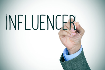 influencer: closeup of the hand of a young caucasian man in suit writing the word influencer with a pen in the foreground Stock Photo