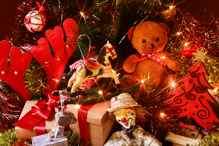 christmas gifts: some gifts and some retro toys, such as a teddy bear, a horse or a marionette, under a christmas tree ornamented with lights, balls and tinsel