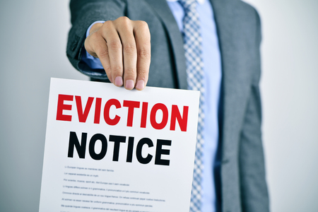 eviction: a young caucasian man wearing a gray suit shows a document with the text eviction notice