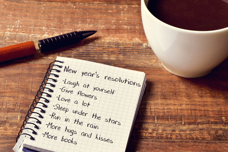new years day: a cup of coffee and a notebook with a list of new years resolutions, such as laugh at yourself, give flowers, love a lot, sleep under the stars or run in the rain, on a rustic wooden table