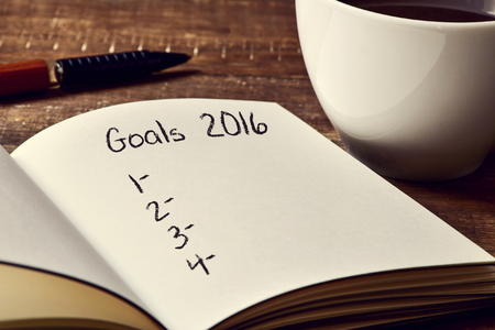 1 2 years: closeup of a notebook with a blank list of goals for 2016 and a cup of coffee on a rustic wooden table Stock Photo