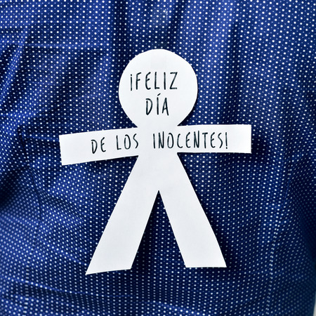 equivalent: young man with a paper man in his back with the text feliz dia de los inocentes, happy innocents day in spanish, a feast held in spain, hispanic america and philippines equivalent to april fools day