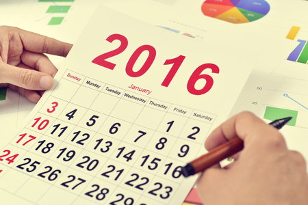 headman: a young caucasian businessman at his office desk full of charts observes a 2016 calendar