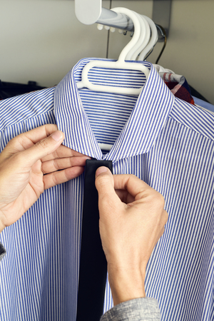 formal dressing: closeup of a young caucasian man choosing a tie and a shirt from the closet