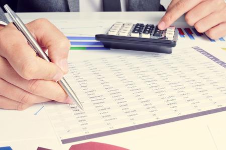 crisis economica: primer plano de una joven que controla negocios caucásico cuentas con una calculadora en su oficina Foto de archivo