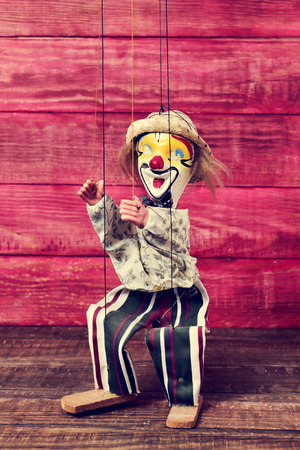 puppet master: an old marionette with its face painted like a clown being manipulated on a red rustic wooden surface Stock Photo