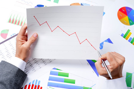 closeup of a young caucasian businessman at his office desk full of graphs and charts observing a chart with a downward trend