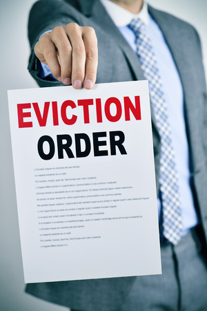 eviction: a young caucasian man wearing a gray suit shows a document with the text eviction order Stock Photo