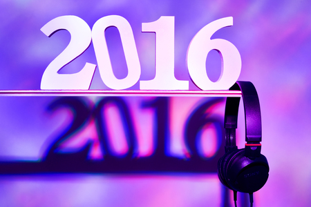 swagger: three-dimensional numbers forming the number 2016, as the new year, and a pair of headphones in a dance club Stock Photo