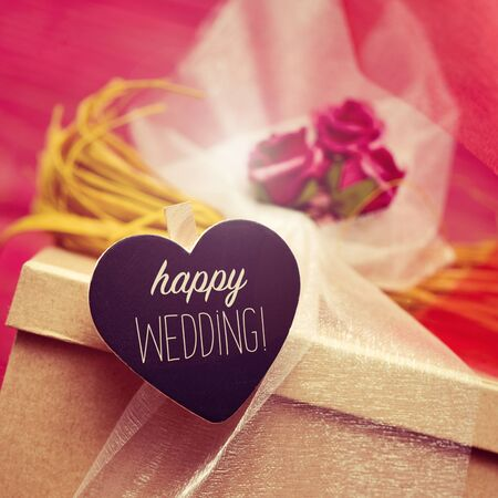 happy wedding: closeup of a gift box ornamented with flowers and tulle, and a heart-shaped black chalkboard with the text happy wedding Stock Photo