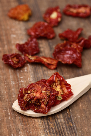 sundried: a pile of sun-dried tomatoes on a rustic wooden table Stock Photo