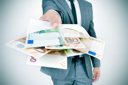 회색 양복을 입고 젊은 백인 남자는 관찰자에 유로 지폐의 전체 봉투를 제공합니다